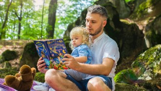 Picture of dad and little boy reading outdoors